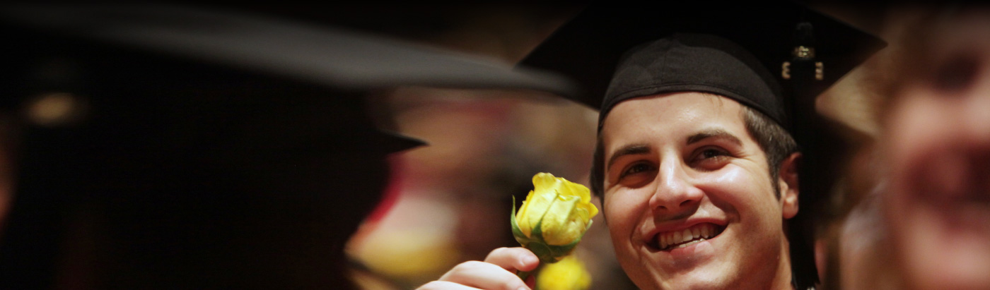 student at graduation with a rose background